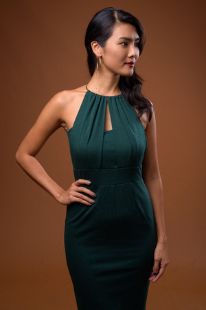 Studio shot of beautiful Asian businesswoman against brown backg