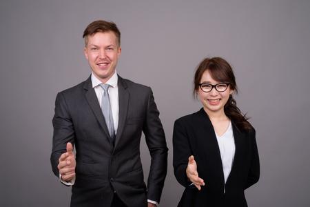 Jeune homme d'affaires et jeune femme d'affaires asiatique contre bac gris Banque d'images