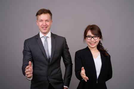 Young businessman and young Asian businesswoman against gray bac Banco de Imagens
