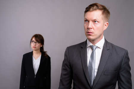 Young businessman and young Asian businesswoman against gray bac Reklamní fotografie