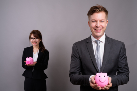 Joven empresario y joven empresaria asiática contra bac gris