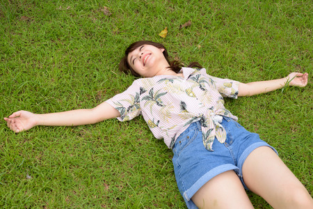 Young beautiful Asian tourist woman relaxing at the park Banco de Imagens