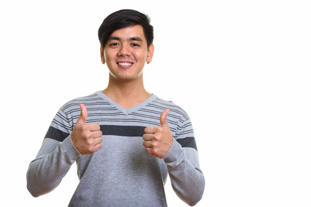 Studio shot of happy Asian man smiling and giving thumbs up