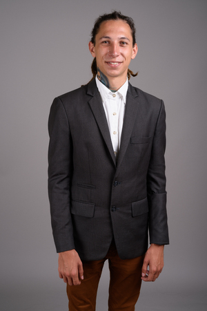 Young businessman with dreadlocks against gray background Imagens