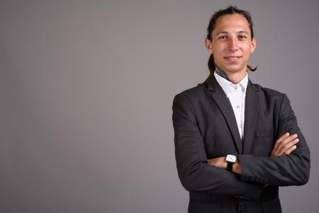 Junger Geschäftsmann mit Dreadlocks vor grauem Hintergrund