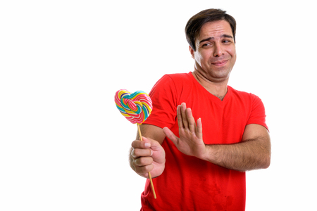 Studio shot of young Persian man holding heart shaped lollipop a Фото со стока