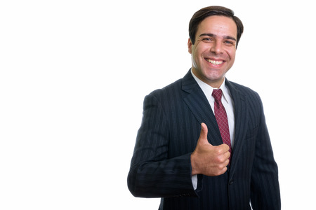 Studio shot of young happy Persian businessman smiling while giv