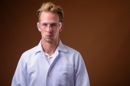 Young handsome man doctor wearing protective glasses against brown