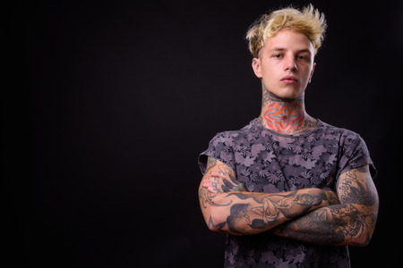Studio shot of young handsome rebellious man with blond hair and tattoos against black background