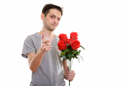 Studio shot of young man holding red roses while pointing at cam