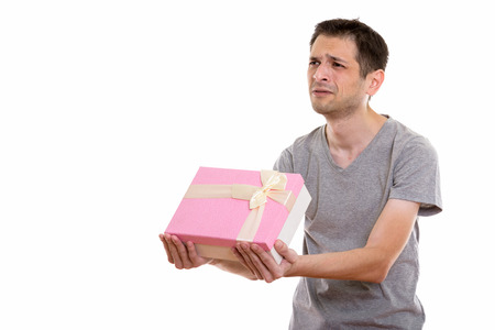 Studio shot of sad young man giving gift box ready for Valentine Stock Photo