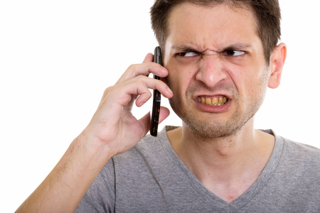Close up of angry young man talking on mobile phone