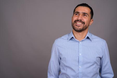Guapo empresario persa barbudo contra el fondo gris