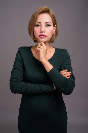 Portrait of beautiful Asian businesswoman against gray background Banco de Imagens - 124590037