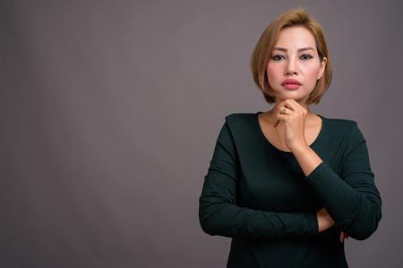 Portrait of beautiful Asian businesswoman against gray background Banco de Imagens - 124590038