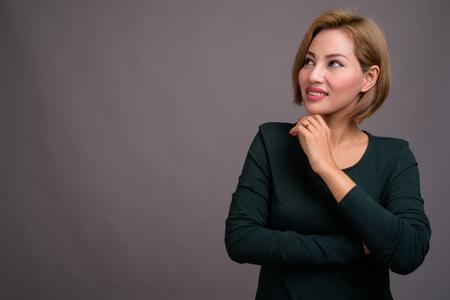 Portrait of beautiful Asian businesswoman against gray background Banco de Imagens - 124590040