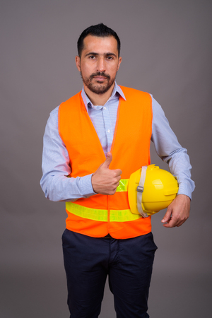 Handsome bearded Persian man construction worker against gray ba Banco de Imagens