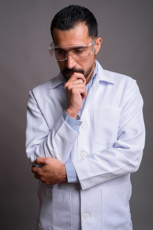 Handsome bearded Persian man doctor wearing protective glasses a Banco de Imagens