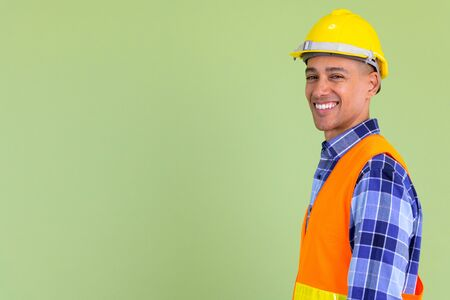 Profile view of happy multi ethnic man construction worker looking at camera