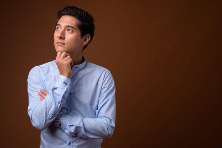 Młody wieloetniczny przystojny biznesmen przeciw brązowi