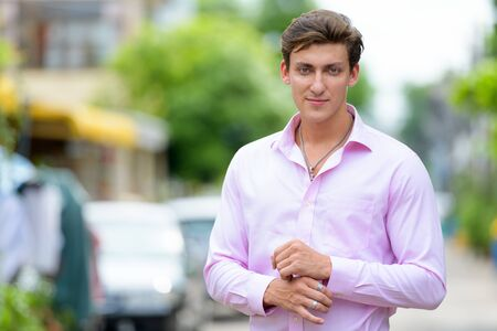 Portrait of young handsome businessman wearing pink shirt outdoors