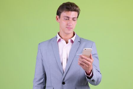 Young handsome businessman in suit using phone