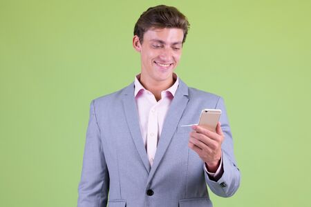 Happy young handsome businessman in suit using phone