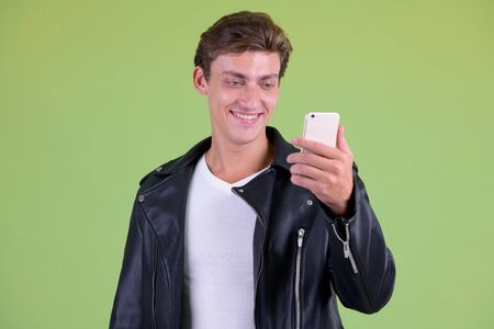Portrait of young happy rebellious man using phone