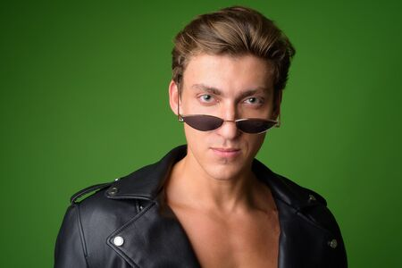 Face of young handsome rebellious man wearing leather jacket and sunglasses