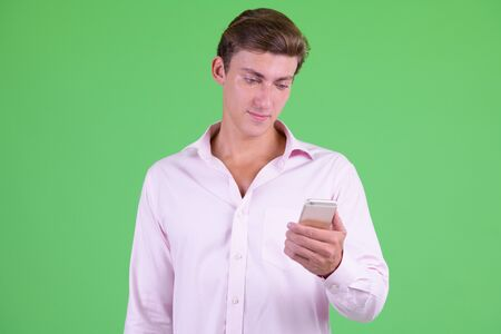 Portrait of young handsome businessman using phone Stock Photo