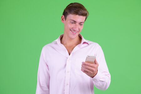 Portrait of young happy businessman using phone