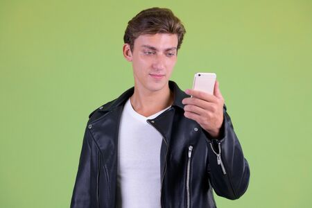 Portrait of young handsome rebellious man using phone Stock Photo