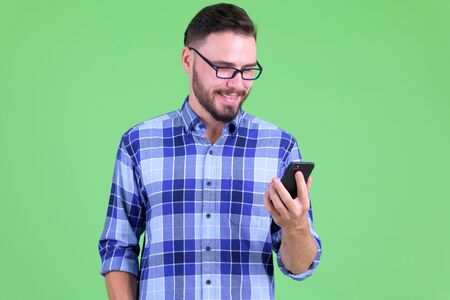 Happy young handsome bearded hipster man using phone