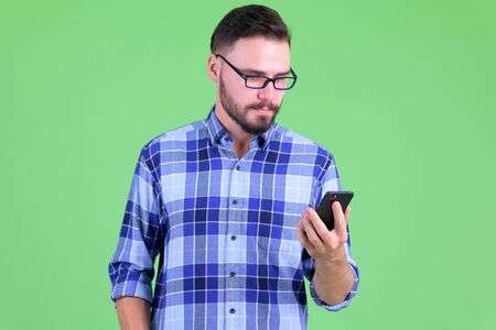Young handsome bearded hipster man using phone