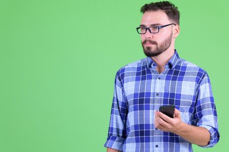 Young handsome bearded hipster man thinking while using phone