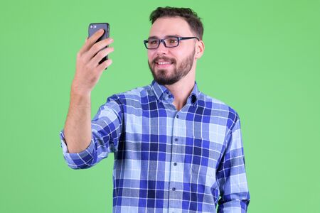 Happy young bearded hipster man taking selfie