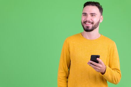 Happy young handsome bearded man thinking while using phone