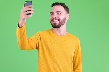 Happy young handsome bearded man taking selfie