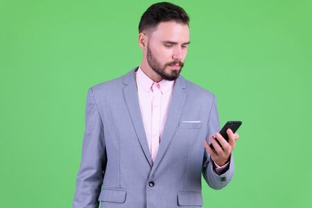 Portrait of young handsome bearded businessman using phone