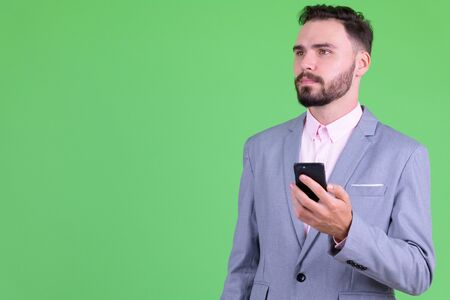 Young handsome bearded businessman thinking while using phone 写真素材