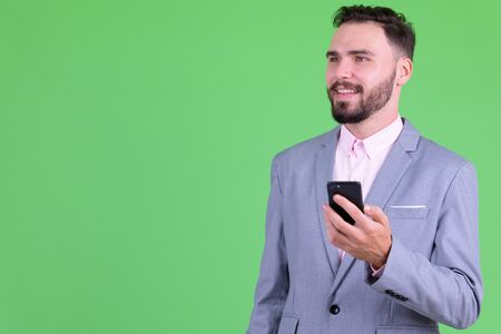 Happy young bearded businessman thinking while using phone