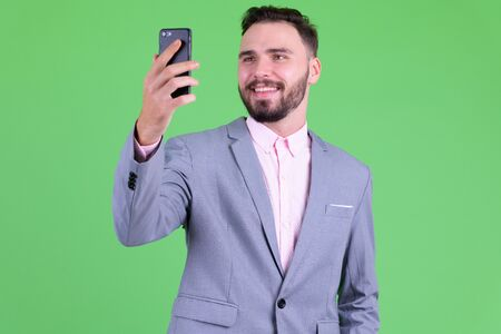 Happy young handsome bearded businessman taking selfie Foto de archivo - 129176721
