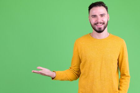 Happy young handsome bearded man showing something Foto de archivo - 129176724