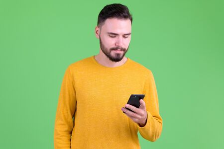 Portrait of young handsome bearded man using phone