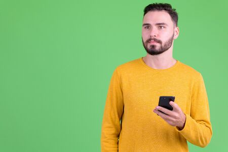 Young handsome bearded man thinking while using phone