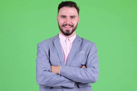 Happy young handsome bearded businessman smiling with arms crossed Foto de archivo - 129176770