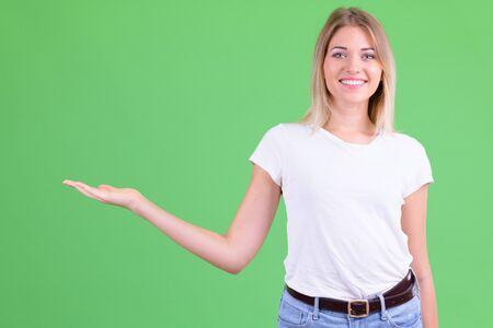 Happy young beautiful blonde woman showing something Foto de archivo - 129176783