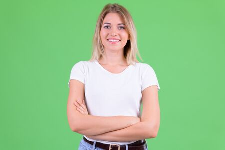 Happy young beautiful blonde woman smiling with arms crossed Foto de archivo - 129176782