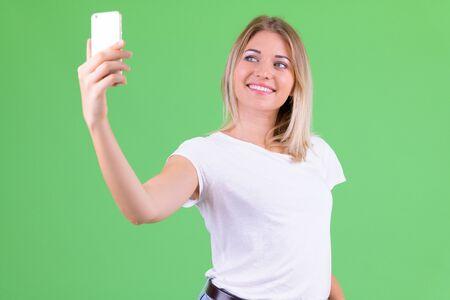 Happy young beautiful blonde woman taking selfie