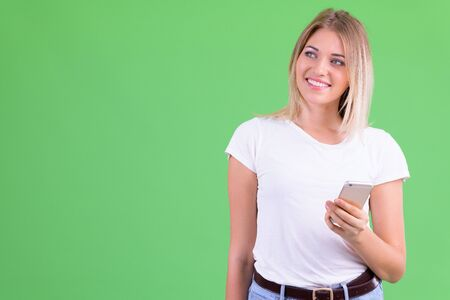 Happy young beautiful blonde woman thinking while using phone